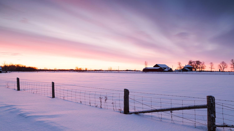 Sunrise behind barn in winter